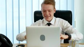 Бизнесмен работая на компьтер-книжке, радуется и смех, уча хорошие новости видеоматериал