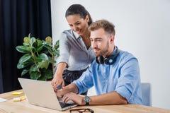 Бизнесмен работая на компьтер-книжке с усмехаясь коллегой в офисе Стоковая Фотография