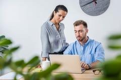 Бизнесмен работая на компьтер-книжке с усмехаясь коллегой в офисе Стоковые Фотографии RF