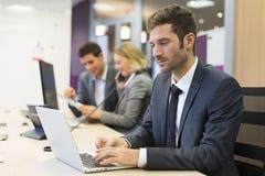 Бизнесмен работая на компьютере в современном офисе, коллегах внутри Стоковая Фотография RF