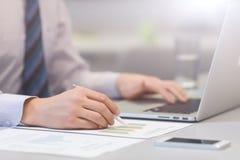 Бизнесмен работая на компьютере и напечатанных диаграммах Стоковая Фотография