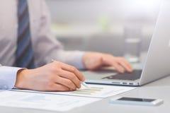 Бизнесмен работая на компьютере и напечатанных диаграммах Стоковые Фото
