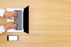 Бизнесмен работая на компьютере и писать в домашнем офисе В стоковая фотография