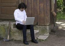 Бизнесмен работая на компьютере пока сидящ на шагах Стоковые Фотографии RF