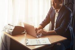 Бизнесмен работая на компьютере на столе окнами Стоковые Изображения RF