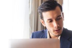 Бизнесмен работая на компьютере на столе окнами Стоковое Фото