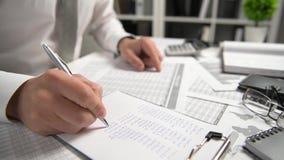 Бизнесмен работая на офисе и высчитывая финансы, читает и пишет отчеты концепция финансового учета дела сток-видео