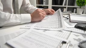 Бизнесмен работая на офисе и высчитывая финансы, читает и пишет отчеты концепция финансового учета дела видеоматериал