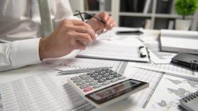 Бизнесмен работая на офисе и высчитывая финансы, читает и пишет отчеты концепция финансового учета дела акции видеоматериалы