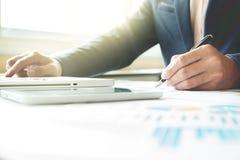 Бизнесмен работая на офисе с dat компьтер-книжки, таблетки и диаграммы Стоковое Изображение