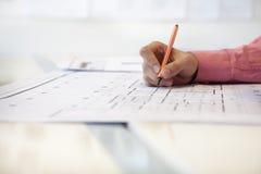 Бизнесмен работая на проекте в офисе, конце архитектуры вверх на руке Стоковая Фотография RF