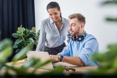 Бизнесмен работая на проекте с усмехаясь коллегой в офисе Стоковое Изображение RF