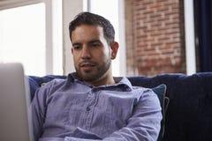 Бизнесмен работая на софе в современном творческом офисе Стоковые Фотографии RF