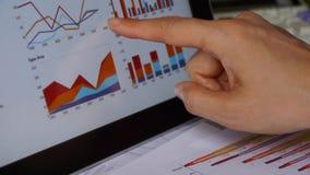 Бизнесмен работая на таблетке с диаграммами, долевыми диограммами финансов пальца касающими видеоматериал
