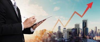 Бизнесмен работая на цифровой таблетке, с видом на город панорамы и поднимая вверх диаграмму и стрелку, представляя рост дела Стоковое Изображение