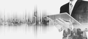 Бизнесмен работая на цифровой таблетке с городом Бангкока двойной экспозиции, концепциями развития биснеса недвижимости