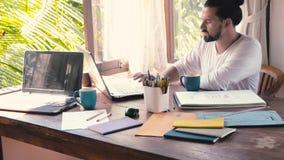 Бизнесмен работая дома или творческий офис с компьтер-книжкой и думая идеей акции видеоматериалы