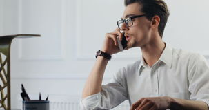 Бизнесмен работая с бумагами и smartphone в офисе портрет юриста 4k закона красивый красивый видеоматериал