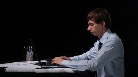 Бизнесмен работая с его компьтер-книжкой на черноте сток-видео