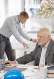 Бизнесмен работая с коллегаом в предпосылке стоковые изображения