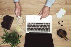 Бизнесмен работая с компьтер-книжкой, дневником и кофейной чашкой на месте для работы Стоковая Фотография