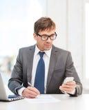Бизнесмен работая с компьтер-книжкой и smartphone Стоковые Изображения RF