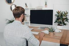 Бизнесмен работая с компьютером на рабочем месте в современном офисе Стоковые Изображения RF