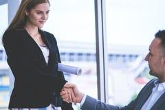 Бизнесмен радостно тряся руку с женским партнером инженера стоковое изображение