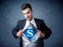 Бизнесмен рвя с его рубашки с знаком супергероя Стоковые Изображения