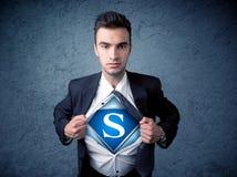Бизнесмен рвя с его рубашки с знаком супергероя Стоковое Изображение