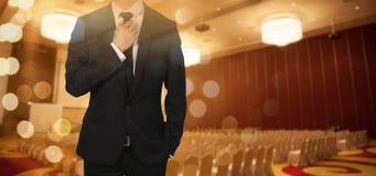 Бизнесмен регулирует галстук показывая доверие в конференц-зале стоковые изображения rf