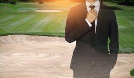 Бизнесмен регулирует галстук показывая доверие в поле для гольфа стоковые фото