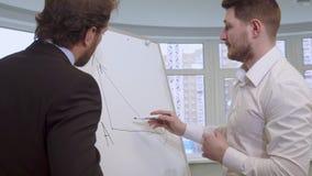 Бизнесмен рисует на диаграмме сальто стоковая фотография rf