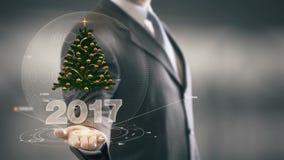 Бизнесмен 2017 рождественской елки держа в новых технологиях руки Стоковое Изображение