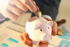 Бизнесмен руки кладя деньги штыря в свинью стоковая фотография