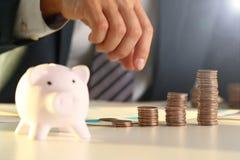 Бизнесмен руки кладя деньги штыря в свинью стоковые фотографии rf