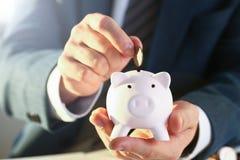 Бизнесмен руки кладя деньги штыря в свинью стоковая фотография rf