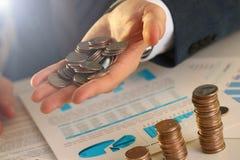 Бизнесмен руки кладя деньги штыря в свинью стоковое фото rf