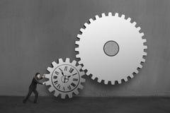 Бизнесмен свертывая большие конкретные шестерни с чертежом часов в c Стоковые Изображения RF