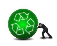 Бизнесмен свертывая большой зеленый шарик с рециркулирует символ на ем I Стоковое фото RF