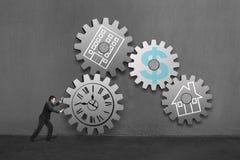 Бизнесмен свертывая большую конкретную шестерню подключает с другими каждым с чертежом часов, офиса, дома и денег Стоковое Изображение