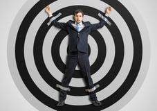 Бизнесмен связан тесьмой к цели с клейкой лентой стоковое фото