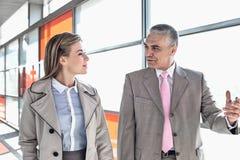 Бизнесмен связывая с женским коллегой пока идущ в железнодорожную станцию Стоковые Изображения