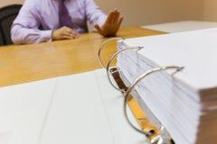 Бизнесмен селективного фокуса молодой в офисе сидя перед выжимк папки для работы стоковые изображения
