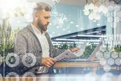 Бизнесмен сидит в кафе на таблице, использует компьтер-книжку и читает газету В переднем плане виртуальные диаграммы, диаграммы,  Стоковые Изображения RF