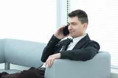 Бизнесмен сидит в лобби офиса и говорить на смартфоне стоковое изображение rf