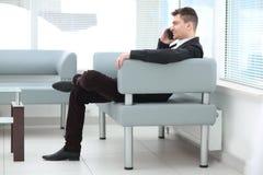 Бизнесмен сидит в лобби офиса и говорить на смартфоне стоковая фотография rf
