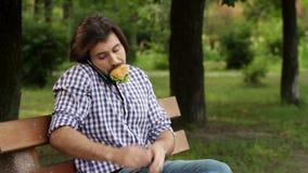 Бизнесмен сидит на bech в парке и говорит на телефоне Он сдерживает часть бургера и продолжает поговорить Человек кладет акции видеоматериалы