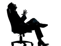 Бизнесмен сидя в кресле ослабляя Стоковое Изображение RF