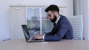Бизнесмен сидя в офисе и печатая на его компьтер-книжке акции видеоматериалы